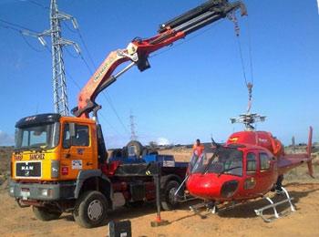 Camión grúa reocgiendo un helicóptero