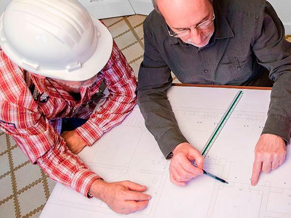 Dos hombres de la construcción estudiando un plano