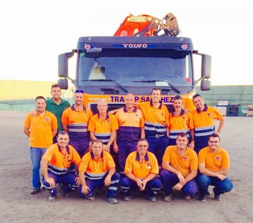El equipo de Transportes Sánchez puestos en dos filas y con un camión detrás