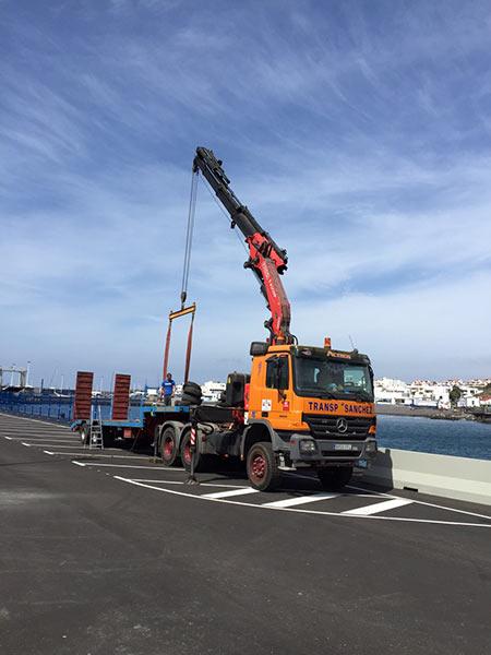 Camión grúa cargando una boya en un puerto